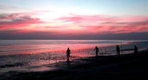 Silhouetten van mensen die voetbal op het strand spelen Stock Afbeelding