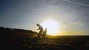 Silhouetten van mensen die voetbal op strand in de lente spelen van, twee kerels die voetbal op zand in de zon spelen stock footage