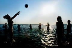 Silhouetten van mensen die volleyball in water spelen Stock Afbeelding