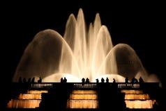 Silhouetten van mensen die zijn tijd doorbrengen bij nacht bij de fontein stock fotografie