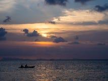 Silhouetten van mensen in een kajak in de stralen van de het plaatsen zon tegen de achtergrond van wolken royalty-vrije stock foto