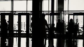 Silhouetten van mensen in moderne zaal stock footage