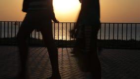 Silhouetten van mensen op de straat Zonsondergang bij het overzees benen stock footage