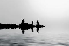 Silhouetten van mensen op rotsen Royalty-vrije Stock Afbeelding