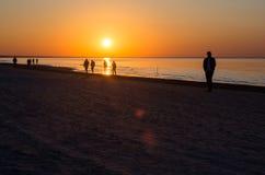 Silhouetten van mensen op zee tijdens zonsondergang royalty-vrije stock foto's