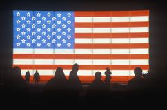 Silhouetten van Mensen voor een Amerikaanse elektrische Vlag, de Winterolympics, Salt Lake City, Utah royalty-vrije stock fotografie
