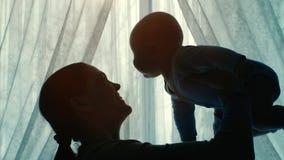 Silhouetten van moeder met een baby stock videobeelden