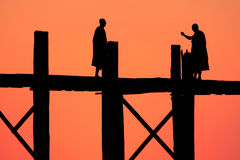 Silhouetten van monniken op de brug bij zonsondergang royalty-vrije stock foto