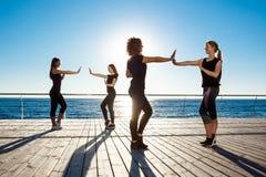 Silhouetten van sportieve meisjes het dansen zumba dichtbij overzees bij zonsopgang Royalty-vrije Stock Afbeelding