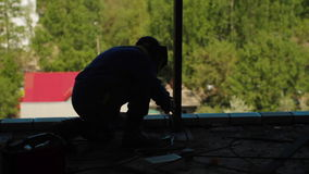 Silhouetten van twee arbeiders die een straal lassen stock video