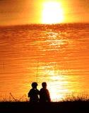 Silhouetten van twee kinderen die op het strand a spelen Royalty-vrije Stock Afbeeldingen