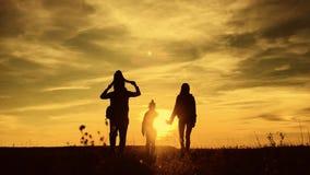 Silhouetten van vader, moeder en kinderen wandeling De baby zit op de schouders van zijn vader De trekking van wandelingsbackpack stock videobeelden