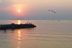 Silhouetten van vissers op golfbreker bij zonsopgang Royalty-vrije Stock Fotografie