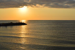 Silhouetten van vissers op golfbreker na zonsopgang Royalty-vrije Stock Foto