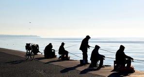 Silhouetten van vissers in Thessaloniki strandboulevard, Griekenland De winter mistig zeegezicht stock fotografie