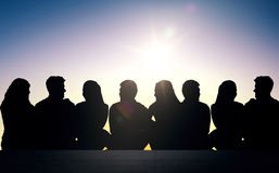 Silhouetten van vrienden die op treden over zon zitten Stock Afbeeldingen