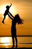Silhouetten van vrouwen en kind op zonsondergang Royalty-vrije Stock Foto's