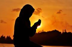 Silhouetten van vrouwen het bidden stock afbeeldingen