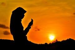 Silhouetten van vrouwen het bidden stock fotografie