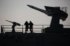 Silhouetten van zeelieden, begroetingskanon en luchtafweerraketsysteem URAGAN in backlight op een achtergrond van avondhemel stock afbeelding