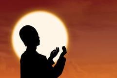 Silhouetteo f muslim praying at sunset. Silhouette of muslim praying at orange sunset Royalty Free Stock Photo