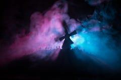 Silhouettes толпа голодных зомби и старой ветрянки на холме против темного туманного тонизированного неба Силуэты страшных зомби  Стоковое Изображение