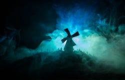 Silhouettes толпа голодных зомби и старой ветрянки на холме против темного туманного тонизированного неба Силуэты страшных зомби  Стоковое Изображение RF