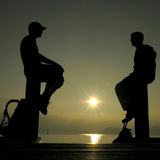 Silhouettes. Of two men against the sun Stock Photo