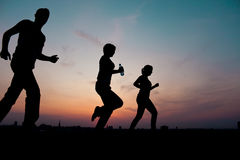 Silhouettes. Group running at sunset Royalty Free Stock Photo
