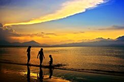 Silhouettes of 3 People in Body of Water during Dawn Stock Photography