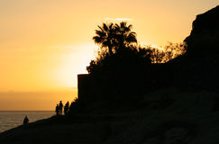 Silhouettes. Of rock, palms and walking people at sunset beach (Tenerife, Canary Islands, Spain Stock Image