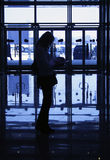 Silhouettes. Silhouette of woman on background of windows in business-centre stock image