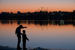 Silhouettes of adult and child at sunset on the river with views of the city and construction cranes. On evening Royalty Free Stock Photos