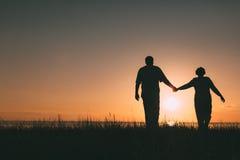 Silhouettes adultes de couples au coucher du soleil Image libre de droits