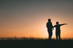 Silhouettes adultes de couples au coucher du soleil Images stock