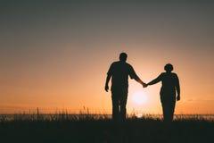 Silhouettes adultes de couples au coucher du soleil Photographie stock libre de droits