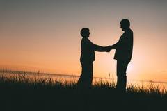 Silhouettes adultes de couples au coucher du soleil Photos libres de droits