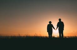 Silhouettes adultes de couples au coucher du soleil Photo libre de droits