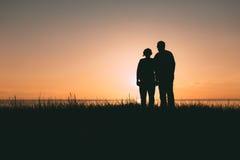 Silhouettes adultes de couples au coucher du soleil Photographie stock