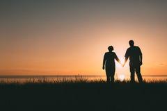 Silhouettes adultes de couples au coucher du soleil Photo stock