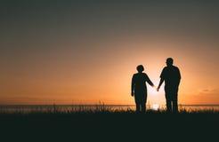 Silhouettes adultes de couples au coucher du soleil Image stock