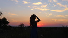 Silhouettes against the sunset young beautiful girl dancing stock video