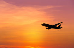 Silhouettes airplane flying on sunset background Stock Photos