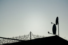 Silhouettes of antennas backlit at sunset Royalty Free Stock Image