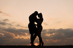 Silhouettes of athletic couple dancing on sunset. Beautiful cloudy sky background.  Royalty Free Stock Photography