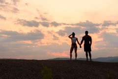 Silhouettes of athletic gymnastic couple watching the sunrise together. Beauty and perfection of human's body Stock Photography