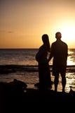 Silhouettes av havandeskapkvinnan på solnedgången Arkivbild