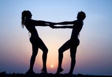 Silhouettes av två kvinnor Arkivfoto