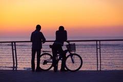 Silhouettes av två män med en cykel Arkivbilder