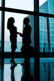 Silhouettes of backlit business people handshake Stock Photos